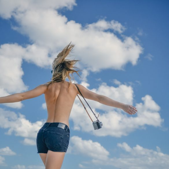 woman with open arms facing the sky representing her found happiness