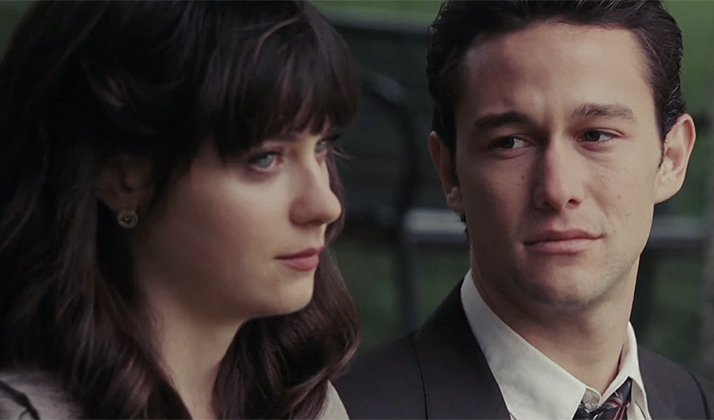 Zooey Deschanel and Joseph Gordon-Levitt sit next to each other as he longingly looks at her