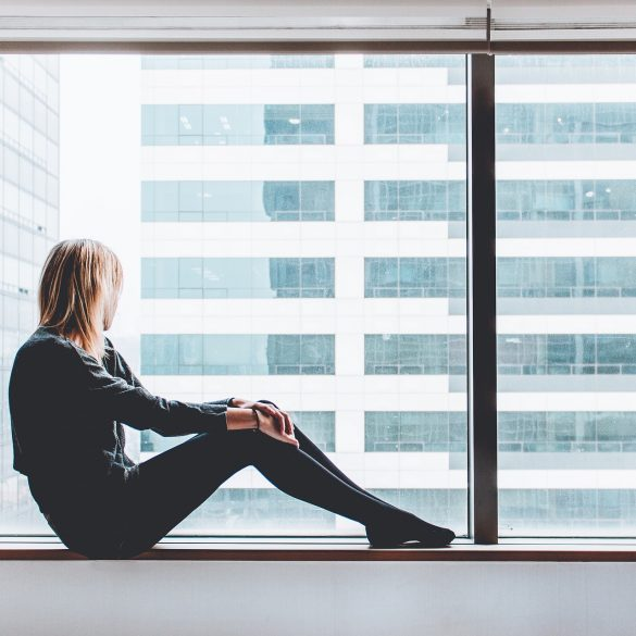woman lookout out a window because she's sad because she sabotages her relationships