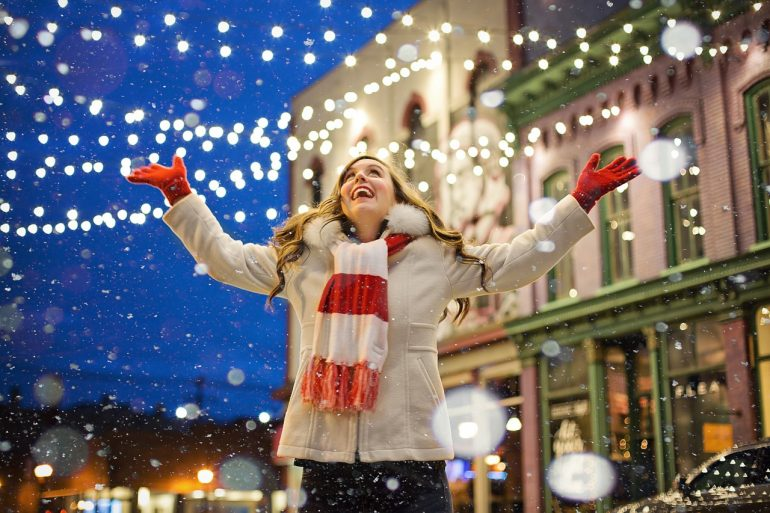 happy single woman wearing a red and white scarf in town decorated in christmas lights