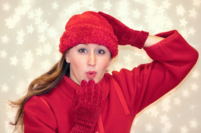woman dressed in red knitted cap, red gloves, and red sweater blowing a kiss in front of a starlit Christmas backdrop