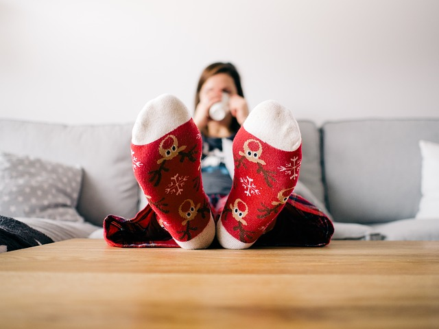 woman sipping cocoa and wearing a pair of red christmas socks with reindeer trying to get through the holidays