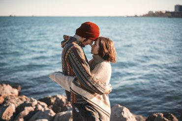 woman who found a good man in an embrace by the ocean side