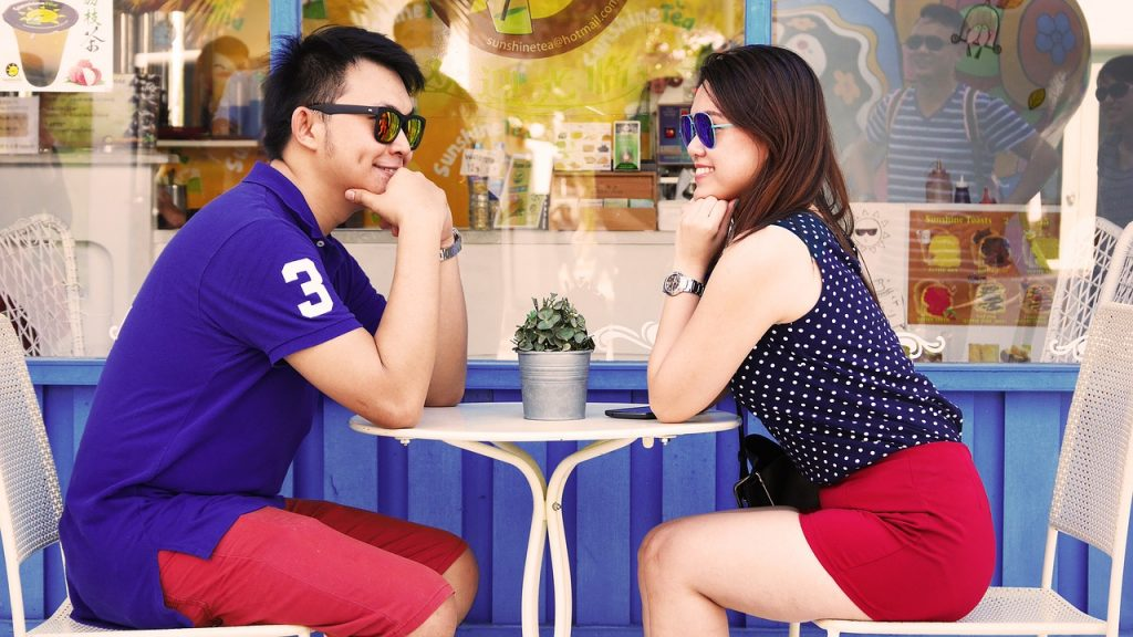 asian man and woman sitting at an outdoor cafe on their first date