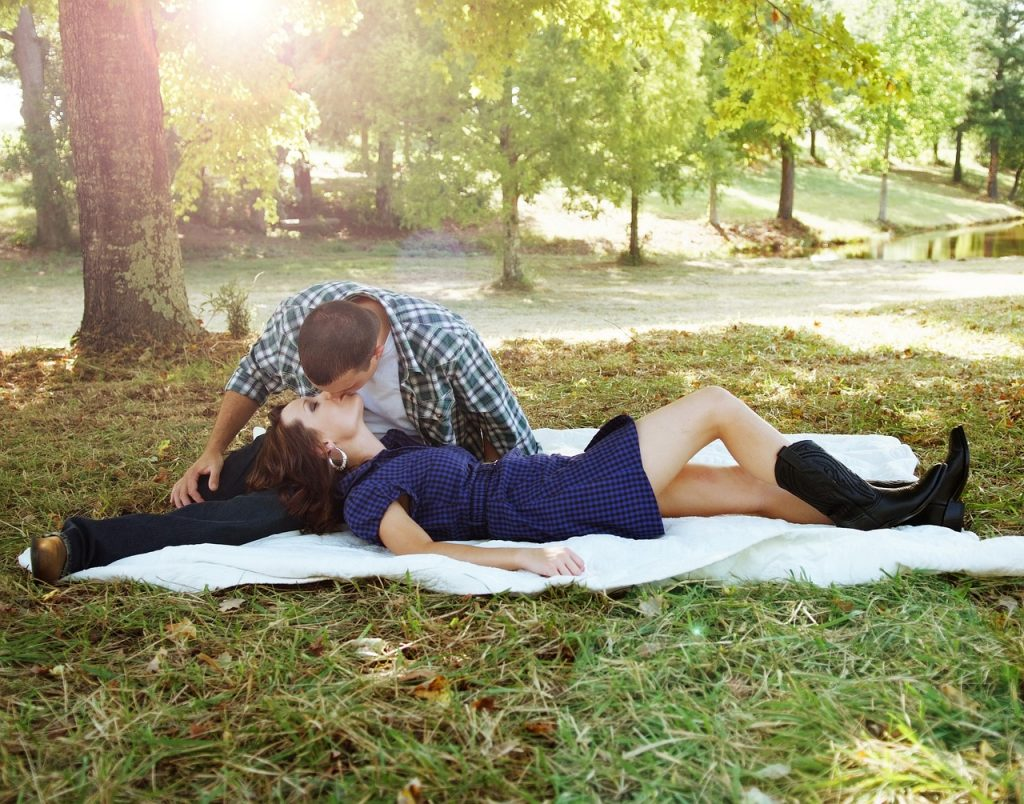 couple kissing while lying on a blanket in a park