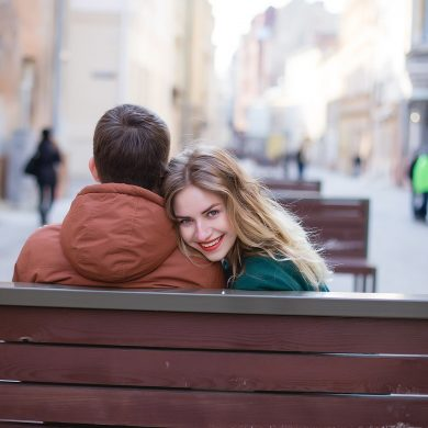 couple sitting on a city bench and woman is looking back and smiling because she is secure in her relationship
