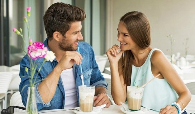 couple on a first date sitting at a table enjoying each other's company and drinking milkshakes and they'll probably go out on a second date