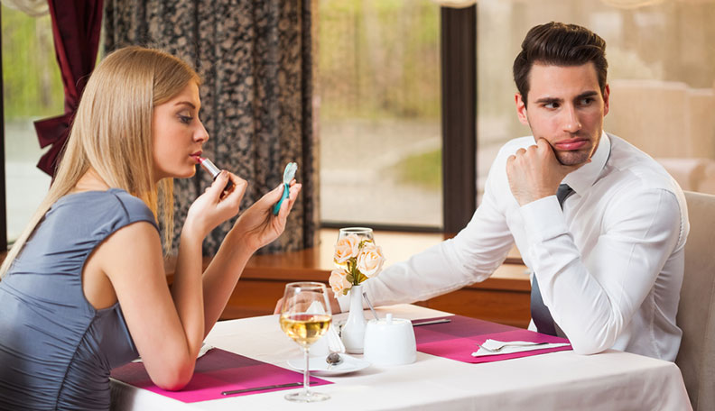 couple on a first date that's not going very well because the woman is putting on lipstick and ignoring the man so they won't go out again