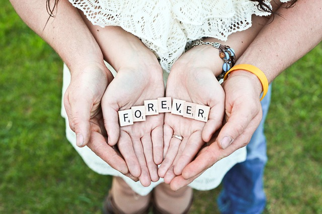 the hands of a couple holding the tiles that say forever to signify monogamy and their devotion to each other