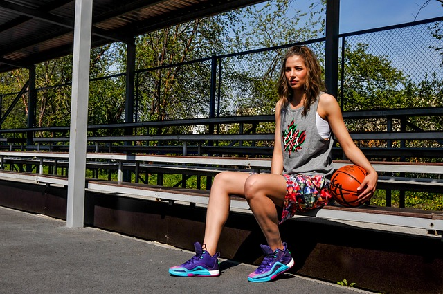 attractive woman sitting at a park holding a basket ball because she's competitive and has just finished playing a game