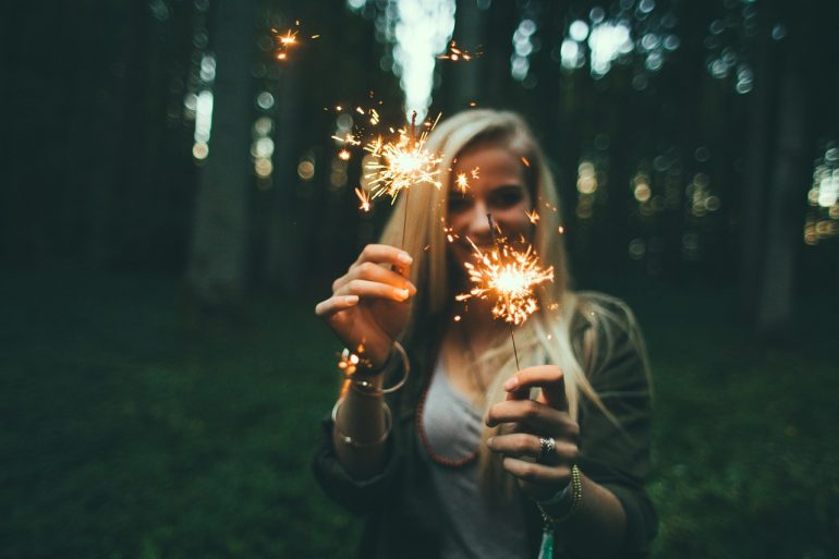 a woman with new year's sparklers smiling because she knows she's going to make changes in the new year to find love and happiness