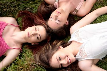 girlfriends laying in the grass
