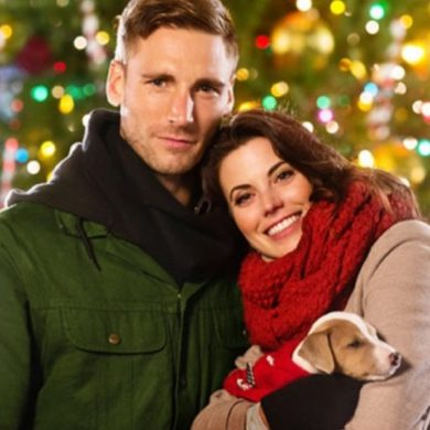 hallmark christmas movie scene with man and woman holding a puppy against a christmas tree decked in lights