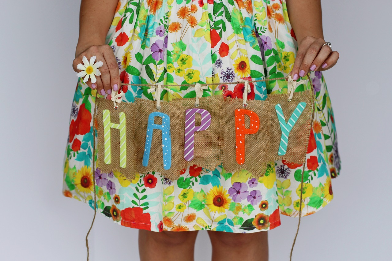 girl in a flowered print dress holding up a sign that says happy