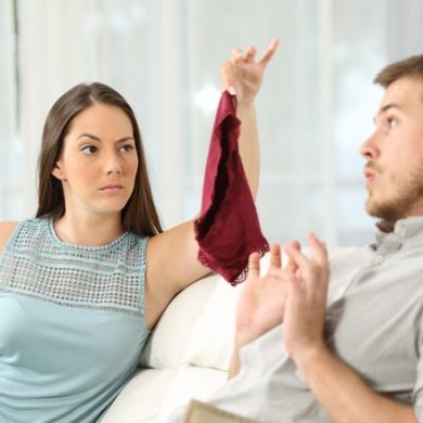 woman holds up a red panty to husband because he's cheating on her