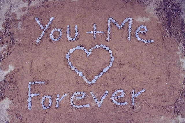 you and me forever written with pebbles in the sand