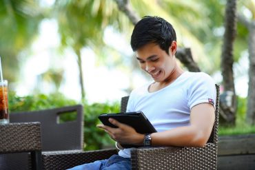 young man looking at his tablet because he is on an online dating site