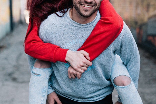 man carrying woman piggyback in a happy relationship