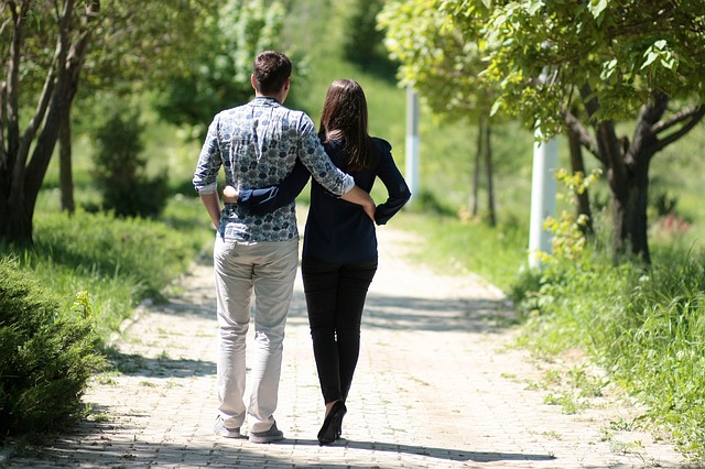 couple walking through the park arm in arm because they are committed to each other exclusively