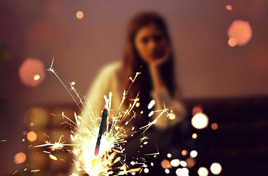mopey woman looking at a sparkler during the holidays because she's lonely