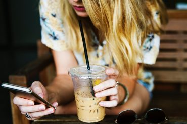 blonde woman drinking a latte and a cell phone in her hand while she's texting her ex-boyfriend