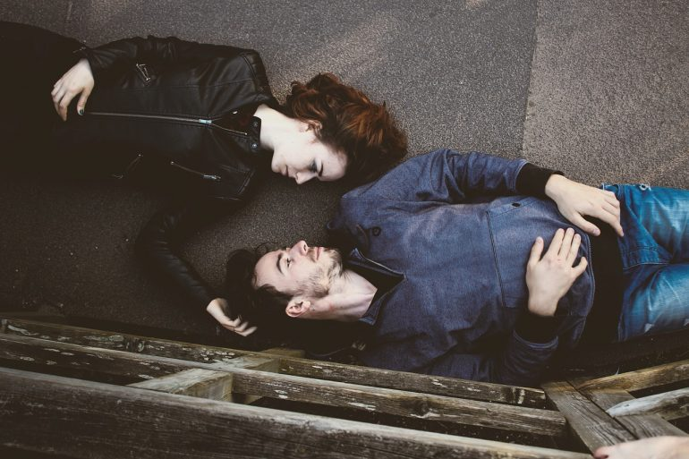 man and woman facing each other lying down