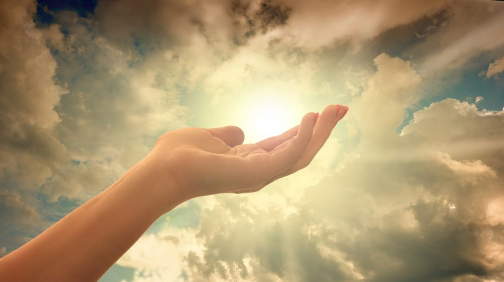 hand lifted up the the clouds and light of the sun breaking through to symbolize healing from the past