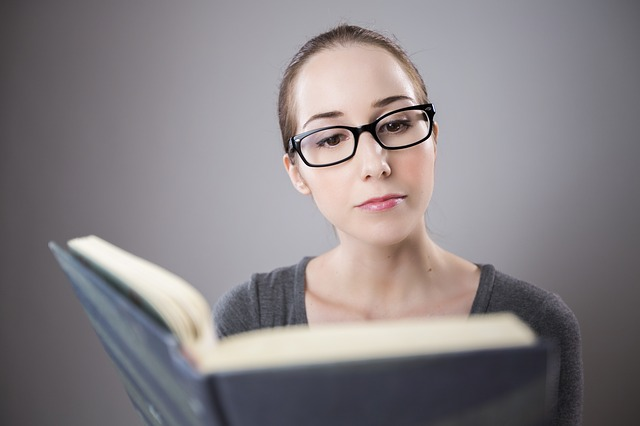 beautiful smart woman wearing glasses and reading a book and she's attractive because of her knowledge