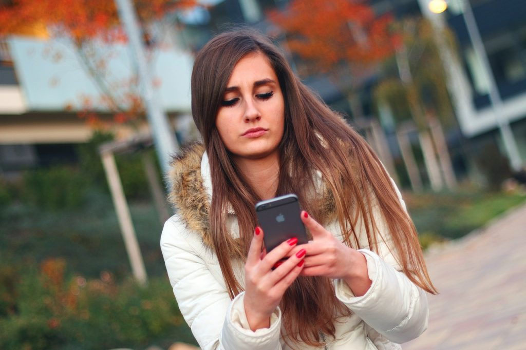 woman on her cell phone looking at her online dating site and being cautious