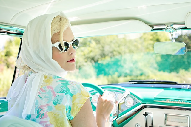 beautiful blonde woman in a vintage automobile with a scarf wrapped around her head and pointy sunglasses like grace kelly