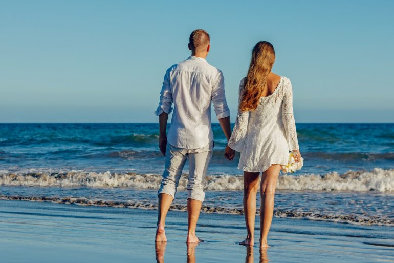 couple walking on the beach who just got married and want to stay married forever