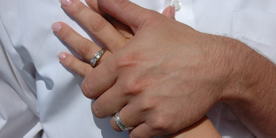 a man's hand holding a woman's hand with a wedding ring representing faithfulness forever