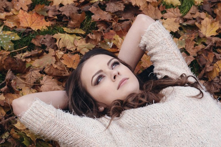 beautiful woman laying on a pile of dried leaves looking up at the sky and contemplating her past and how she can move on