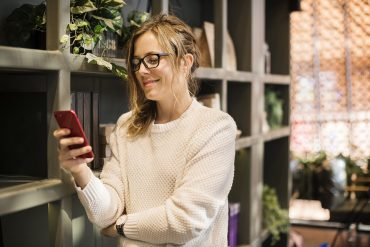 woman looking at her phone because she found a boyfriend online