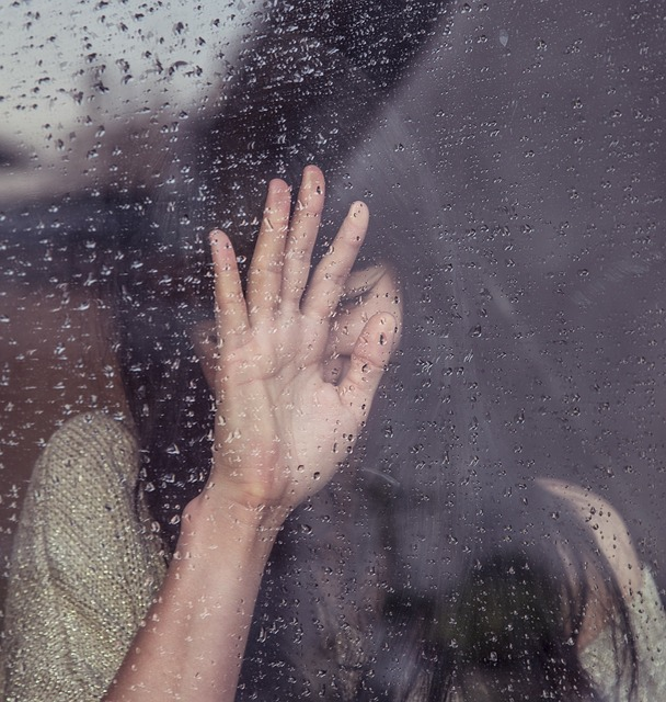woman in emotional pain after a painful breakup looking through a window as it rains
