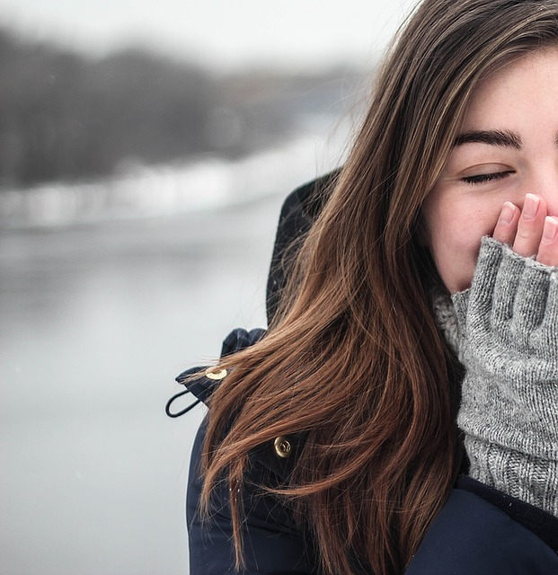 beautiful woman dressed in winter clothes covering her mouth in laughter at her man's funny jokes