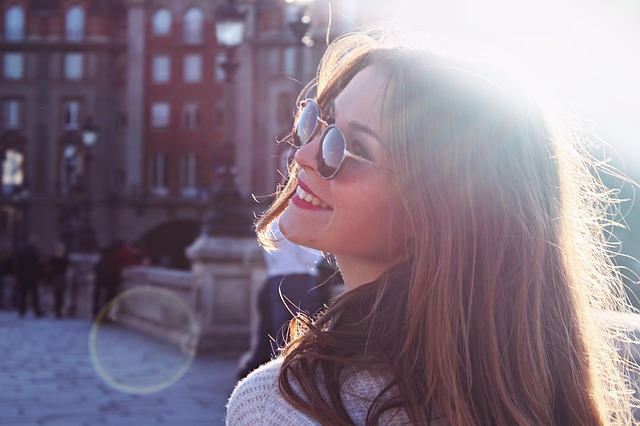 woman in the city with sunshine in her hair and smiling up at the sky because she is starting the new year living in positive intention