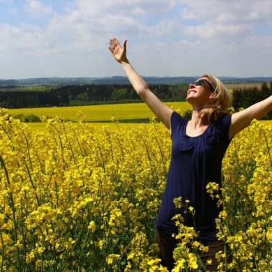 woman in worship mode with her ams uplifted in a field of yellow flowers because she has manifested a miracle
