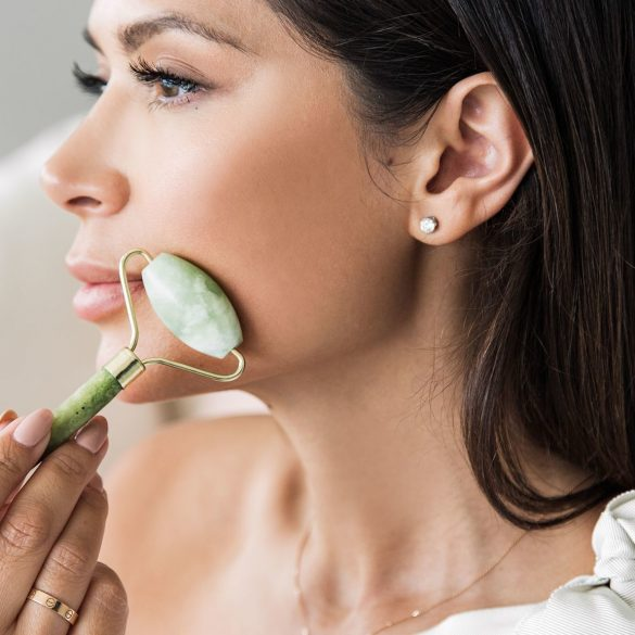 woman demonstrating the benefits of using a jade roller on her face
