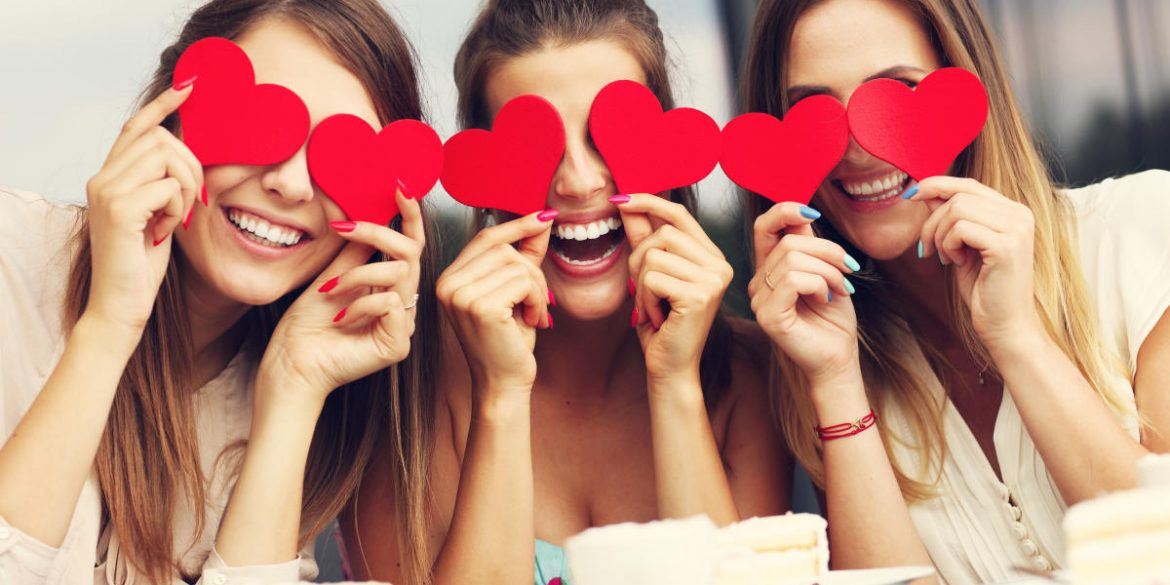 three girlfriends celebrating galentine's day by holding hearts over their eyes