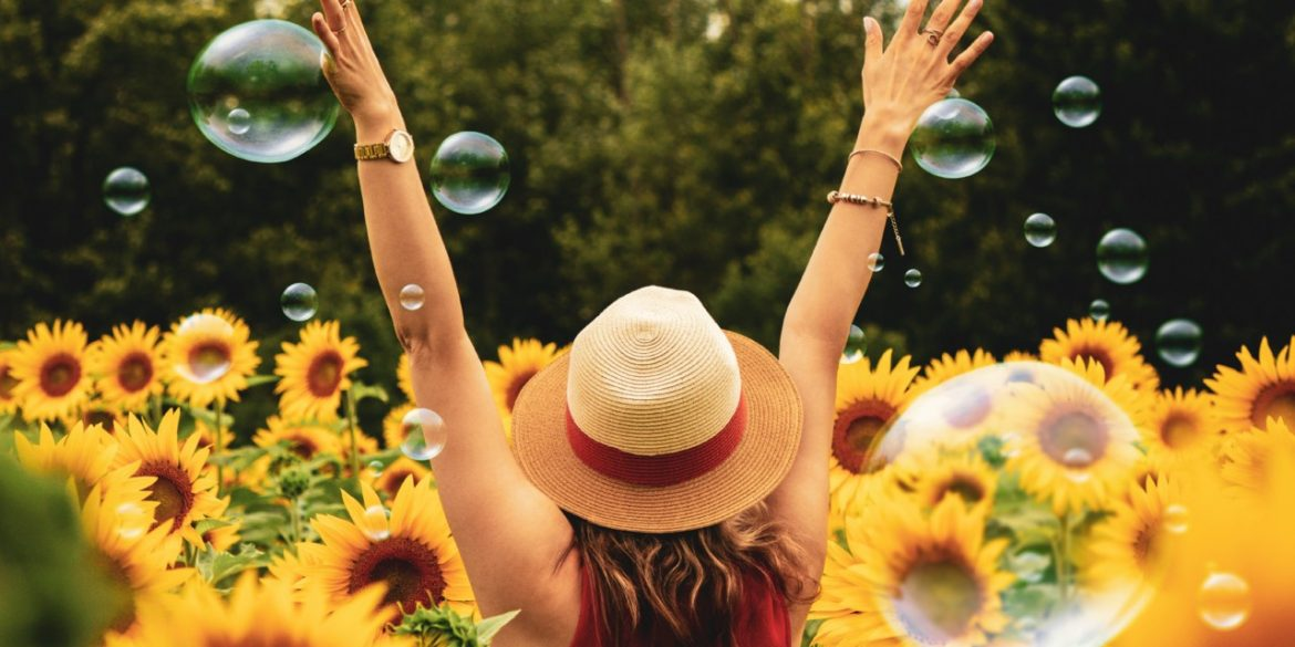 woman living life in a state of happiness this side of happy in a sunflower field