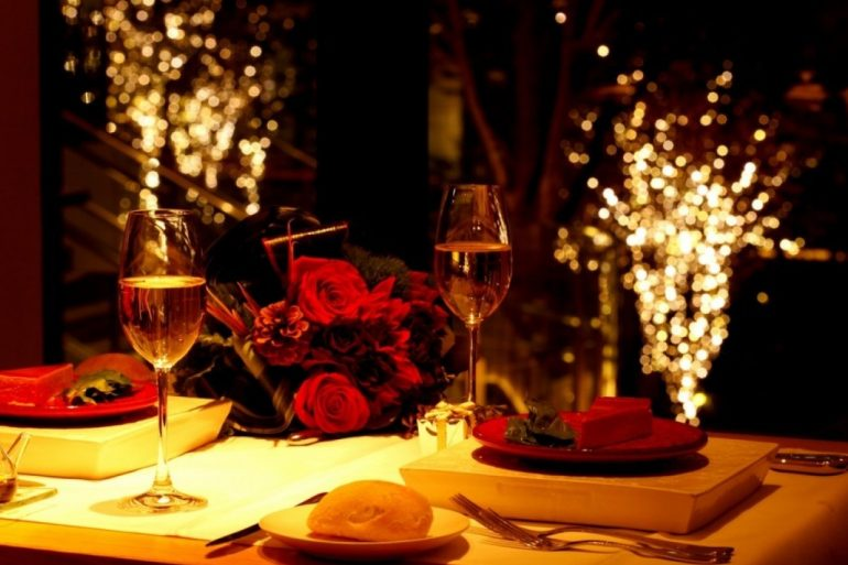 table set with wine and red decorations for amateur hour at restaurant for valentine's day