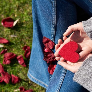 woman sitting on the ground and holding a red valentine's day heart because she is stressed and lonely on Valentine's Day
