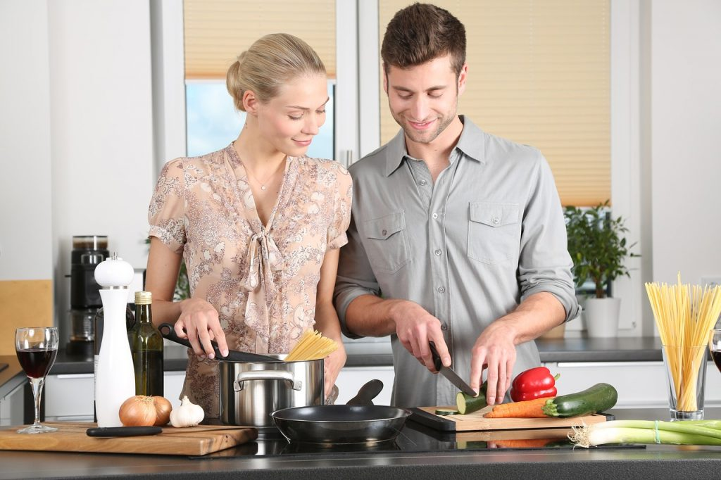 couple in their kitchen preparing a romantic dinner together instead of going out on Valentine's Day