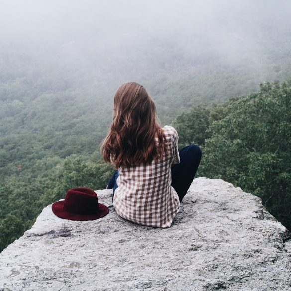 woman feeling self love while sitting on a mountain top