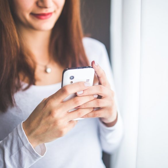 young woman on a cell phone texting a guy to let him know she's not interested but doing it in a kind way