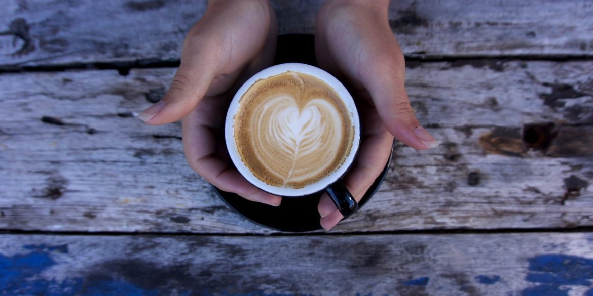 a woman's hands holding a cup of coffee to show the fat burning benefits of coffee