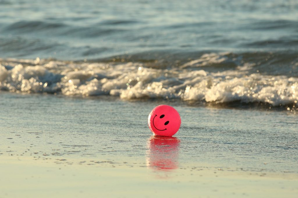 c'mon get happy with a ball on the beach
