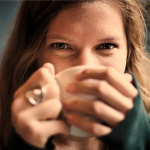happy woman drinking a cup of tea and implementing good habits to be happier and healthier